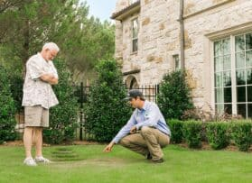 Weedex technician speaking with a customer about their lawn treatment service